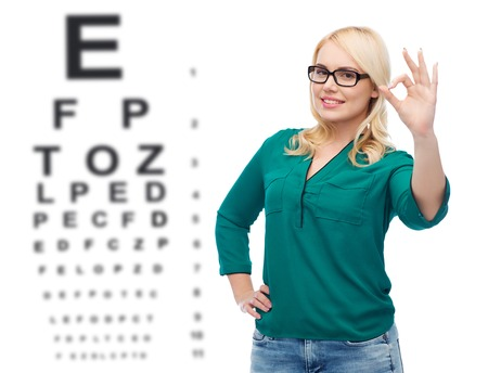 vision, ophthalmology, optics, health care and people concept - smiling young woman with eyeglasses showing ok over eye chart background