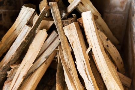 heating, warmth and coziness concept - close up of firewood in fireplace