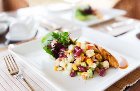 voedsel, koken en eten concept - close-up van vlees met bijgerecht op bord in restaurant Stockfoto