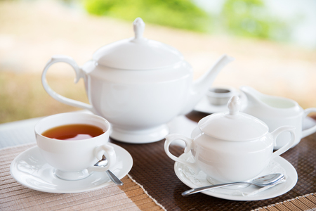 tea service: teatime, drink and object concept - close up of tea service on table at restaurant or teahouse