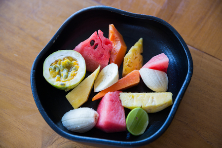 sliced watermelon: food, eco, bio and summer holidays concept - close up of exotic tropical fruits in bowl