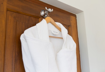 bathtime: bath, clothes, hygiene and luxury concept - close up of two white bathrobes hanging on wooden hanger at home or hotel
