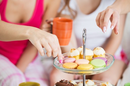 pajama party: friendship, people, pajama party and junk food concept - close up of friends or teenage girls eating sweets from cake stand at home