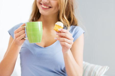friendship, people, pajama party and junk food concept - close up of happy woman or teen girl with tea cup eating cupcake at home Stock Photo