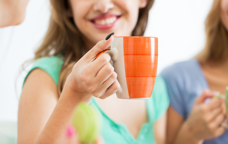 party friends: people and drinks concept - close up of happy woman or teen girl drinking tea from cup