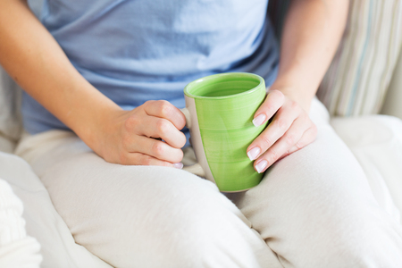 pj's: people and drinks concept - close up of young woman with tea cup