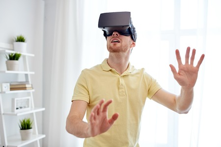 technology, gaming, entertainment and people concept - young man with virtual reality headset or 3d glasses playing video game Stock Photo