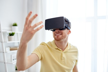 technology, gaming, entertainment and people concept - happy young man with virtual reality headset or 3d glasses playing video game Stock Photo