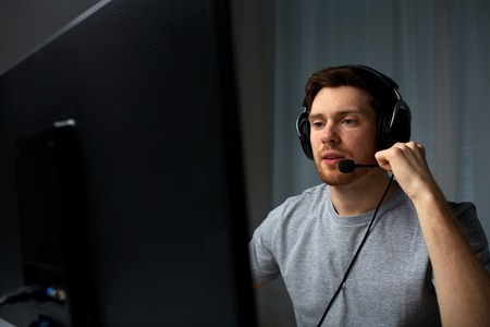 lets: technology, gaming, entertainment, lets play and people concept - young man in headset with pc computer playing game at home and streaming playthrough or walkthrough video