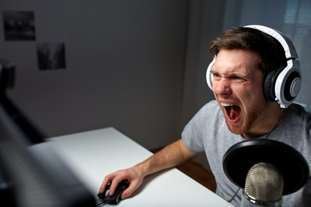lets: technology, gaming, entertainment, lets play and people concept - angry screaming young man in headset with pc computer playing game at home and streaming playthrough or walkthrough video