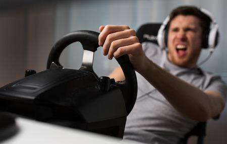 technology, gaming, entertainment, lets play and people concept - close up of angry young man in headphones with pc computer playing car racing video game at home and steering wheel Stock Photo