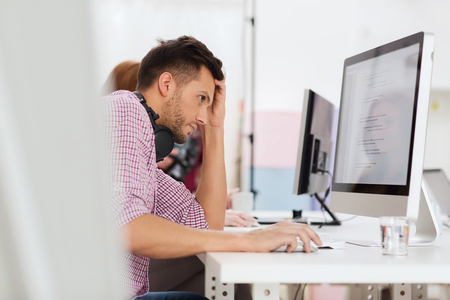 deadline, startup, education, technology and people concept - sad stressed software developer or student with headphones and computer at office 版權商用圖片