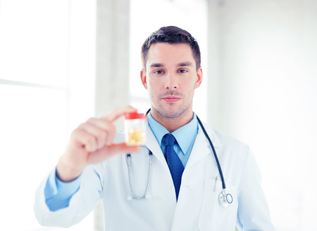 picture of young male doctor with jar of capsules