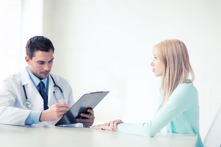 prescribing: healthcare and medical concept - male doctor with patient in hospital