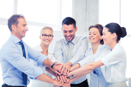 team hands: picture of happy business team celebrating victory in office
