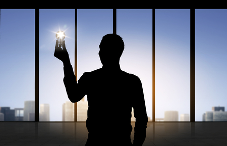 alight: business, inspiration, idea and people concept - silhouette of businessman holding alight light bulb over office window background Stock Photo