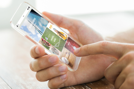 body parts cell phone: business, technology, mass media and people concept - close up of male hand holding transparent smartphone with internet news web page on screen Stock Photo