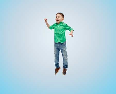 fly: happiness, childhood, freedom, movement and people concept - happy little boy jumping in air over blue background Stock Photo