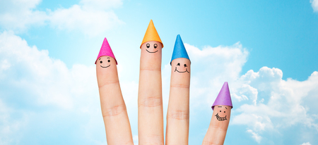 gesture, family, holidays and body parts concept - close up of hand showing four fingers with party hats over blue sky and clouds background