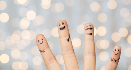 four people: gesture, family, people and body parts concept - close up of four fingers with smiley faces over holidays lights background