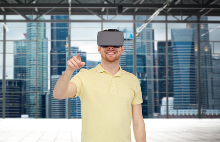 mediated: 3d technology, virtual reality, entertainment and people concept - happy young man with virtual reality headset or 3d glasses playing game over industrial empty room and city panorama background