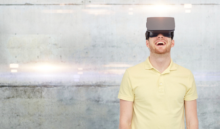 mediated: 3d technology, virtual reality, entertainment and people concept - happy young man with virtual reality headset or 3d glasses over gray concrete wall background