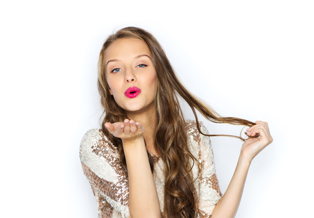 blow kiss: people, style, holidays, hairstyle and fashion concept - happy young woman or teen girl in fancy dress with sequins and long wavy hair sending blow kiss