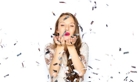 woman blowing: people, holidays, gesture and glamour concept - happy young woman or teen girl in fancy dress with sequins and confetti at party sending blow kiss Stock Photo