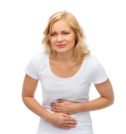 people, healthcare and problem concept - unhappy woman suffering from stomach ache Stock Photo