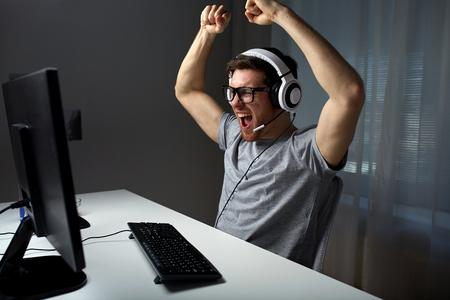 Technologie, Spiele, Unterhaltung, lassen Sie uns spielen und Menschen Konzept - glückliche junge Mann in den Brillen mit Headset zu spielen und zu gewinnen Computerspiel zu Hause und Streaming Spielen oder Lösungsvideo