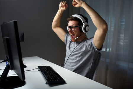 video gaming: technology, gaming, entertainment, lets play and people concept - happy young man in eyeglasses with headset playing and winning computer game at home and streaming playthrough or walkthrough video
