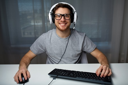technology, gaming, entertainment, lets play and people concept - happy smiling young man in eyeglasses with headset playing computer game at home and streaming playthrough or walkthrough video
