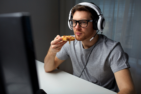 computer gaming: technology, gaming, entertainment, lets play and people concept - young man in headset with pc computer eating pizza while playing game at home and streaming playthrough or walkthrough video