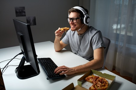 gamer: technology, gaming, entertainment, lets play and people concept - happy young man in headset with pc computer eating pizza while playing game at home and streaming playthrough or walkthrough video Stock Photo