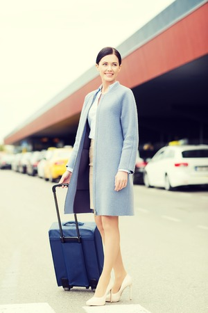 travel bag: travel, business trip, people and tourism concept - smiling young woman with travel bag over taxi at airport terminal or railway station