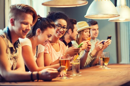 happy african: people, leisure, friendship, technology and communication concept - group of happy smiling friends with smartphones and drinks at bar or pub