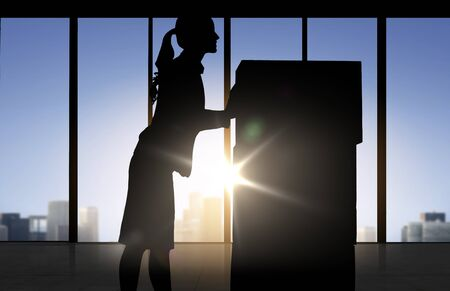 moving office: business, logistics, transportation and shipment people concept - silhouette of businesswoman moving boxes over office window background Stock Photo