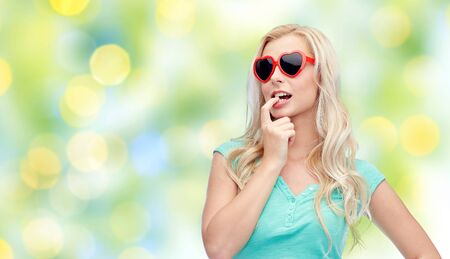 deciding: emotions, expressions, summer and people concept - smiling young woman or teenage girl in sunglasses over summer green lights background