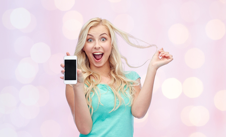 mujer alegre: emotions, expressions, technology and people concept - smiling young woman or teenage girl showing blank smartphone screen over pink holidays lights background