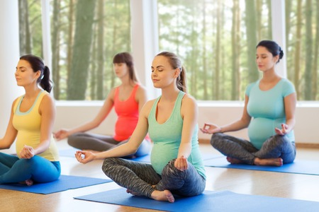 pregnancy yoga: pregnancy, sport, fitness, people and healthy lifestyle concept - group of happy pregnant women exercising yoga and meditating in lotus pose in gym