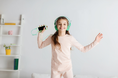 in pajama: people, children, pajama party and technology concept - happy smiling girl in headphones jumping on bed with smartphone and listening to music at home