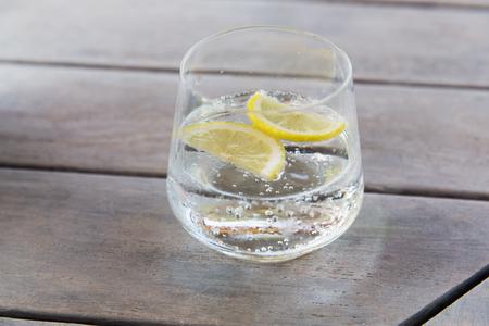 drinken en verfrissing concept - glas mousserende water met citroen segmenten op tafel Stockfoto