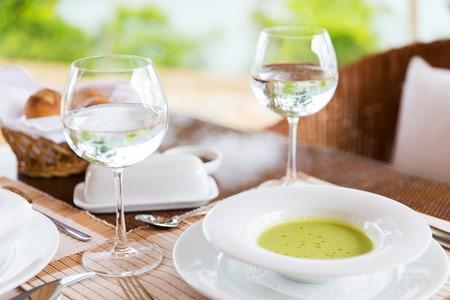 vasos de agua: alimentos, cocinar y comer concepto - cerca de cremosos vasos de sopa y agua sobre la mesa en el restaurante o en el hogar Foto de archivo