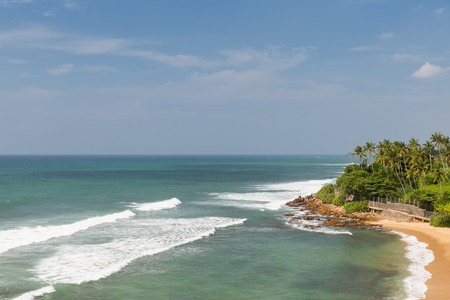 costal: travel, tourism, vacation, seascape and summer holidays concept - sea or ocean waves and blue sky on Sri Lanka beach