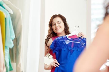 服、ワードローブ、ファッション、スタイル、人々 コンセプト - プラスサイズの女性ミラー自宅でハンガーにドレスで幸せ