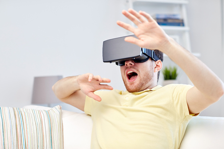 mediated: 3d technology, virtual reality, gaming, entertainment and people concept - scared young man with virtual reality headset or 3d glasses playing game Stock Photo