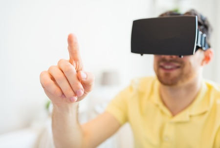 entertainment concept: 3d technology, virtual reality, entertainment and people concept - close up of happy young man with virtual reality headset or 3d glasses playing game at home