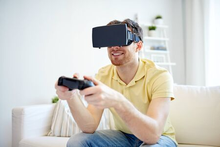 technology, gaming, entertainment and people concept - happy young man with virtual reality headset or 3d glasses playing video game with controller gamepad at home Stock Photo