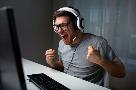 technology, gaming, entertainment, lets play and people concept - happy young man in eyeglasses with headset playing and winning computer game at home and streaming playthrough or walkthrough video
