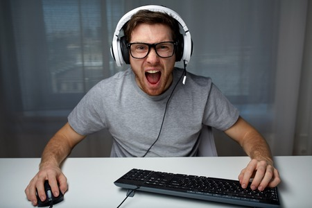 technology, gaming, entertainment, lets play and people concept - angry screaming young man in headset with pc computer playing game at home and streaming playthrough or walkthrough video